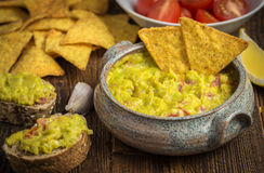 Guacamole in home crafted bowl  with tortilla chips on natural w Stock Photo