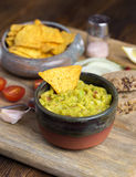 Guacamole in home crafted bowl on wooden desk. Royalty Free Stock Images
