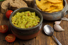 Guacamole in home crafted bowl on wooden desk. Stock Photography