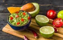 Guacamole i blått bowlar med den tortillachiper och citronen på det naturliga träskrivbordet arkivfoton