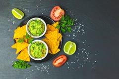 Guacamole i nachos z składnikami na tle czarny kamień wsiadamy obraz royalty free
