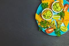Guacamole i nachos z składnikami na tle czarny kamień wsiadamy obrazy royalty free