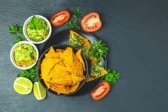 Guacamole i nachos z składnikami na tle czarny kamień wsiadamy fotografia royalty free