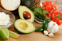Guacamole Ingredients. Fresh avocado surrounded by onion, tomato, garlic, jalepeno peppers and lime, ready for preparing guacamole Royalty Free Stock Photos