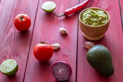 Guacamole and ingredients. Red background. Mexican cuisine stock images