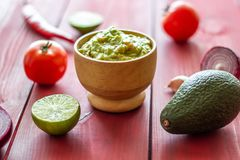 Guacamole and ingredients. Red background. Mexican cuisine royalty free stock photo