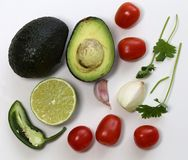 Guacamole Ingredients in a Still Life Photo. Guacamole ingredients in a still live photo. The photo includes avocado, cilantro, tomatoes, lime, jalapeno, onion stock photography