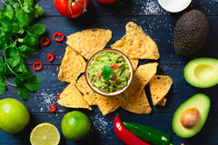 Guacamole with ingredients and tortilla chips Royalty Free Stock Images