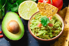 Guacamole with ingredients and tortilla chips Royalty Free Stock Image