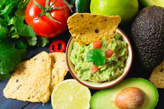 Guacamole with ingredients and tortilla chips Stock Photos