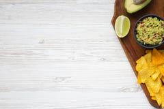 Guacamole med havrenachos, limefrukt, klippt halv avokado på träwhi Arkivbilder