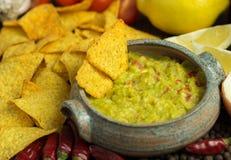Guacamole in naar huis bewerkte kom met tortilla rond spaanders stock afbeelding