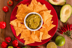 Guacamole and nacho chips. Guacamole and nacho chips on red dish Royalty Free Stock Images