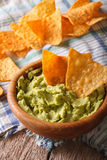 Guacamole and nachos chips close up in a wooden bowl. Vertical Stock Images