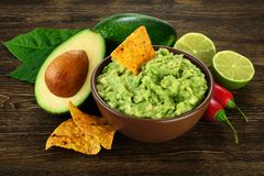 Guacamole nachos and guacamole ingredients on dark wooden background. royalty free stock photo