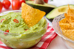 Guacamole with nachos and tomatoe. Guacamole bowl with nachos on white wood Royalty Free Stock Images