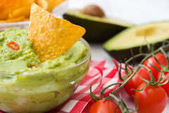 Guacamole with nachos and tomatoe. Guacamole bowl with nachos on white wood Stock Photography