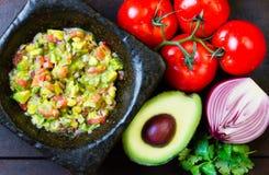 Guacamole no almofariz e nos ingredientes de pedra Vista superior Fotografia de Stock Royalty Free