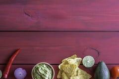 Guacamole- och chipnachos R?d bakgrund tacos f?r gr?n mexikansk s?s f?r kokkonst traditionell kryddig arkivbilder