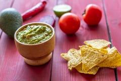 Guacamole- och chipnachos R?d bakgrund tacos f?r gr?n mexikansk s?s f?r kokkonst traditionell kryddig royaltyfria bilder