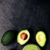 Guacamole with ripe avocados over black background. Top view close up Royalty Free Stock Image
