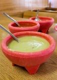 Guacamole, rode saus, molcajete, Mexicaanse sausen in roze ceramische kommen stock fotografie