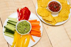 Guacamole and salsa dips. A starter of guacamole, salsa and different dips carrot, pepper and cucumber stock photo