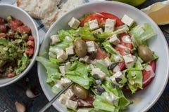 Guacamole - sauce et ingrédients latino-américains avocat, tomates, oignon, citron, ail, chaux et salade verte Photo stock
