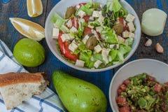 Guacamole - sauce et ingrédients latino-américains avocat, tomates, oignon, citron, ail, chaux et salade verte Photos stock