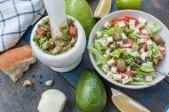 Guacamole - sauce et ingrédients latino-américains avocat, tomates, oignon, citron, ail, chaux et salade verte Image stock