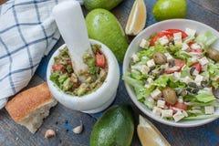 Guacamole - sauce et ingrédients latino-américains avocat, tomates, oignon, citron, ail, chaux et salade verte Images libres de droits