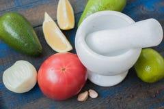 Guacamole - sauce et ingrédients latino-américains avocat, tomates, oignon, citron, ail, chaux sur le fond en bois bleu Images libres de droits