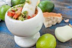 Guacamole - sauce et ingrédients latino-américains avocat, tomates, oignon, citron, ail, chaux sur le fond en bois bleu Photos libres de droits
