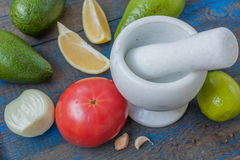 Guacamole - sauce et ingrédients latino-américains avocat, tomates, oignon, citron, ail, chaux sur le fond en bois bleu Photos stock
