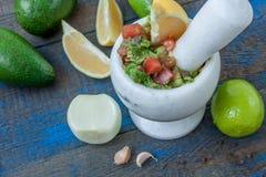 Guacamole - sauce et ingrédients latino-américains avocat, tomates, oignon, citron, ail, chaux sur le fond en bois bleu Photographie stock libre de droits