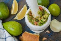 Guacamole - sauce et ingrédients latino-américains avocat, tomates, oignon, citron, ail, chaux sur le fond en bois bleu Photo stock