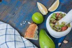 Guacamole - sauce et ingrédients latino-américains avocat, tomates, oignon, citron, ail, chaux sur le fond en bois bleu Image libre de droits