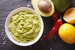 Guacamole sauce with ingredients close-up. horizontal top view Stock Images