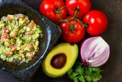 Guacamole in stone mortar and ingredients avocado, tomatoes, onion, cilantro Stock Photos