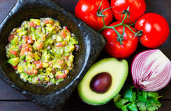 Guacamole in stone mortar and ingredients. Top view Royalty Free Stock Photography