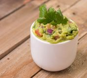 Guacamole. With tomatoes red onions and cilantro in a small bowel on a wooden background Stock Photography