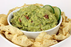 Guacamole with Tortilla Chips. Bowl of guacamole with lime slices on a plate of tortilla chips stock images