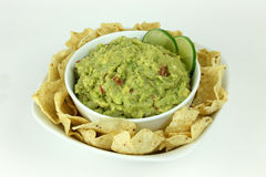 Guacamole with Tortilla Chips. Bowl of guacamole with lime slices on a plate of tortilla chips on an isolated background royalty free stock images