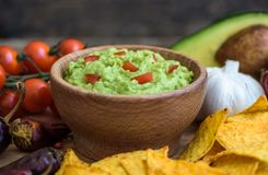 Guacamole with Tortilla Chips. Guacamole in Wooden Bowl with Tortilla Chips and Ingredients Royalty Free Stock Images