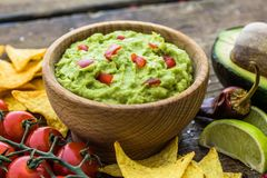 Guacamole with Tortilla Chips and Ingredients Royalty Free Stock Photo