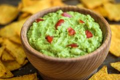 Guacamole with Tortilla Chips. Guacamole in Wooden Bowl with Tortilla Chips Stock Photo