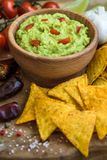 Guacamole with Tortilla Chips. Guacamole in Wooden Bowl with Tortilla Chips and Ingredients Stock Photo