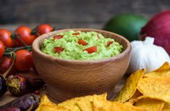 Guacamole with Tortilla Chips. Guacamole in Wooden Bowl with Tortilla Chips and Ingredients Royalty Free Stock Photo
