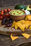 Guacamole with Tortilla Chips. Guacamole in Wooden Bowl with Tortilla Chips and Ingredients Stock Image