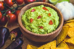 Guacamole with Tortilla Chips. Guacamole in Wooden Bowl with Tortilla Chips and Ingredients Royalty Free Stock Photos